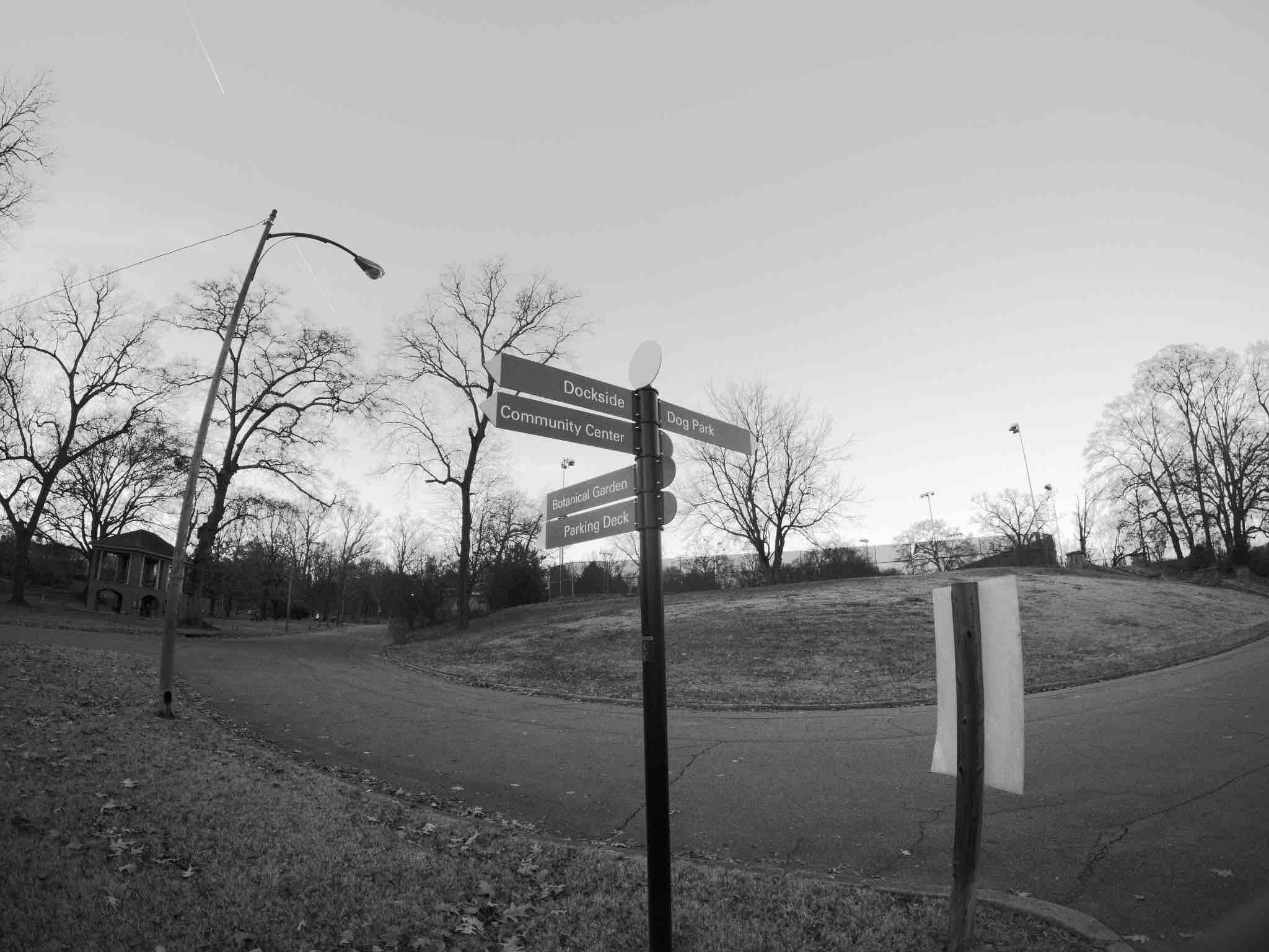 A black-and-white photo of a crossroads-style sign in the middle of Piedmont Park in Atlanta, Georgia.